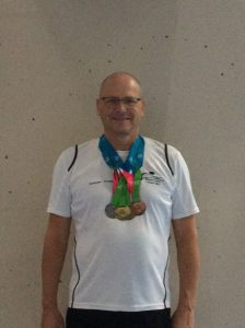 Graham with his full Backstroke medal set; gold, silver, bronze (and one more for his IM)